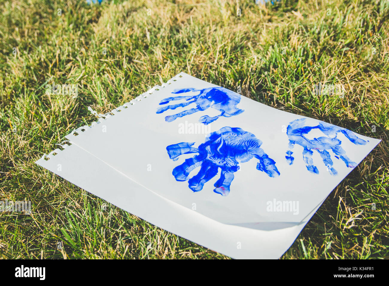 A child's hand prints in blue paint on paper. - Stock Image