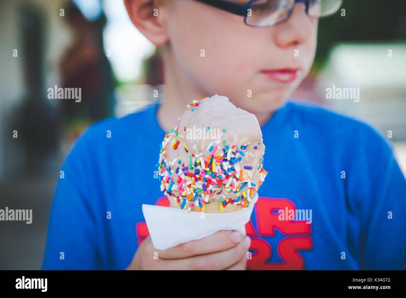 A boy eats an ice cream cone during a warmer season. - Stock Image