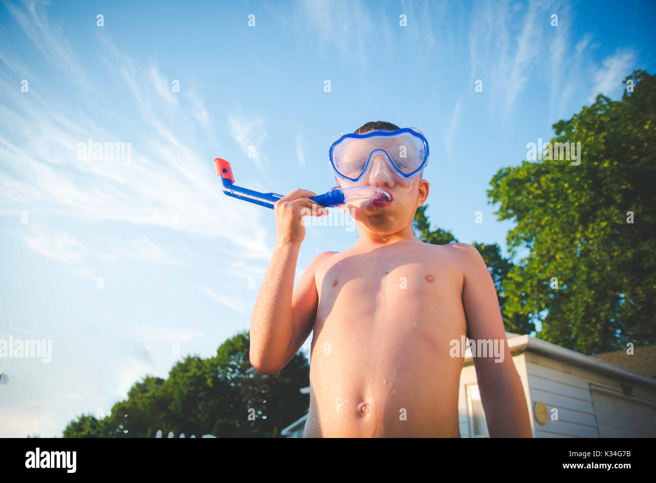 A boy wears a scuba mask against a blue sky with a few clouds. - Stock Image