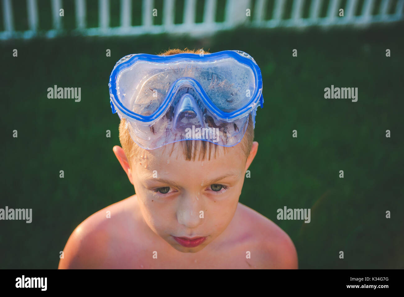 A boy wears a scuba mask on his head during the summer while the sun shines on him. - Stock Image