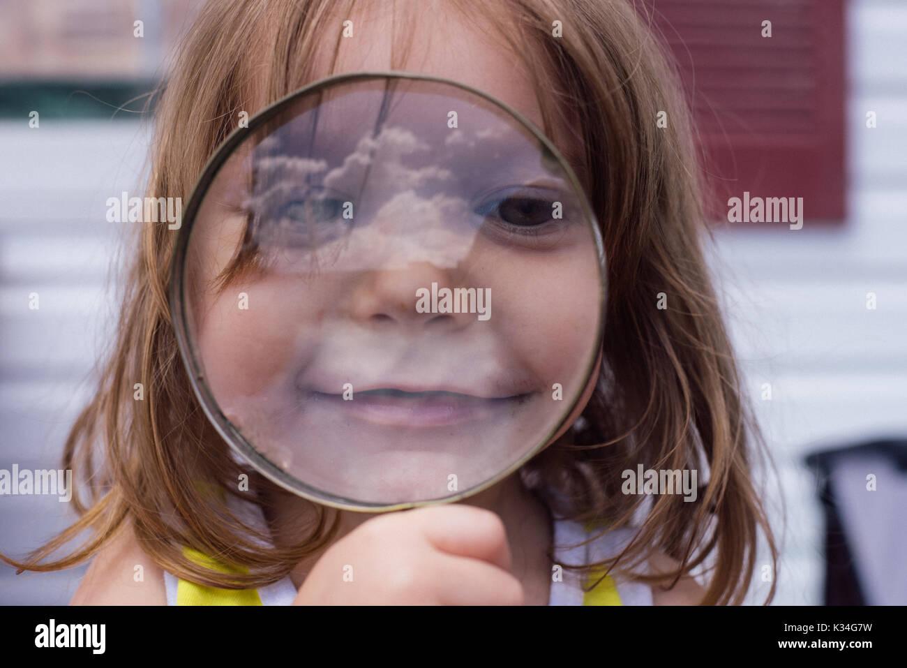 A young girl looks through a circular magnifying glass. - Stock Image