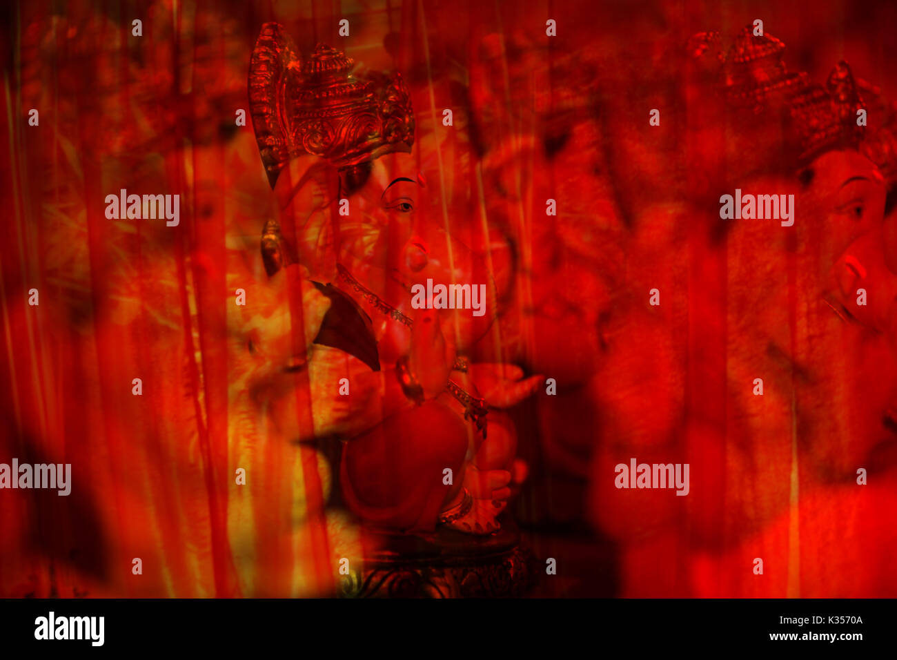 An abstract view of hindu elephant God Ganesha behind red transparent curtain - Stock Image