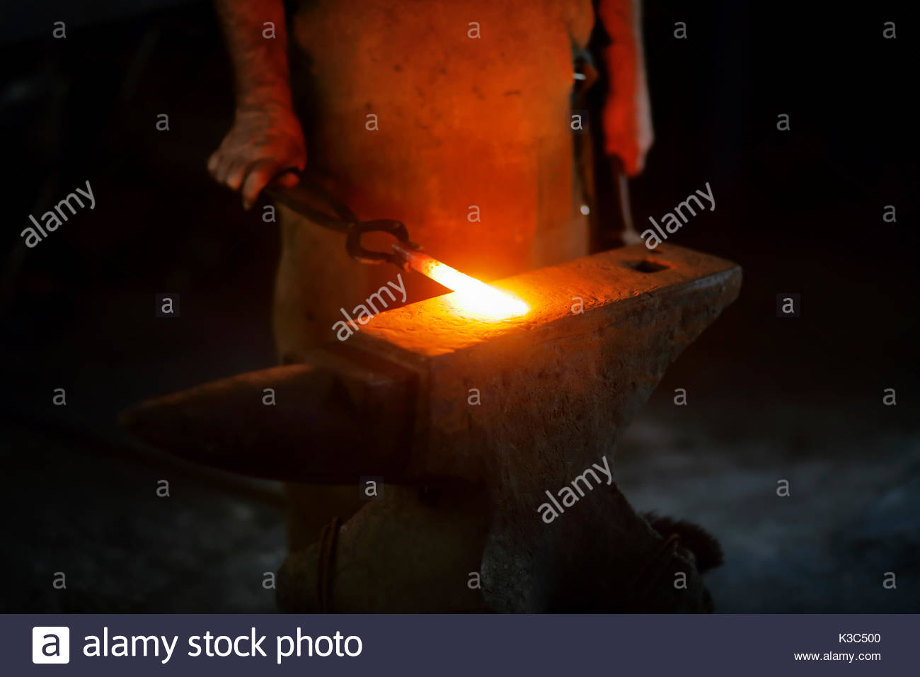 Authentic Old-Fashioned Blacksmith placing red hot iron with pincers on anvil to be hammerred - Stock Image