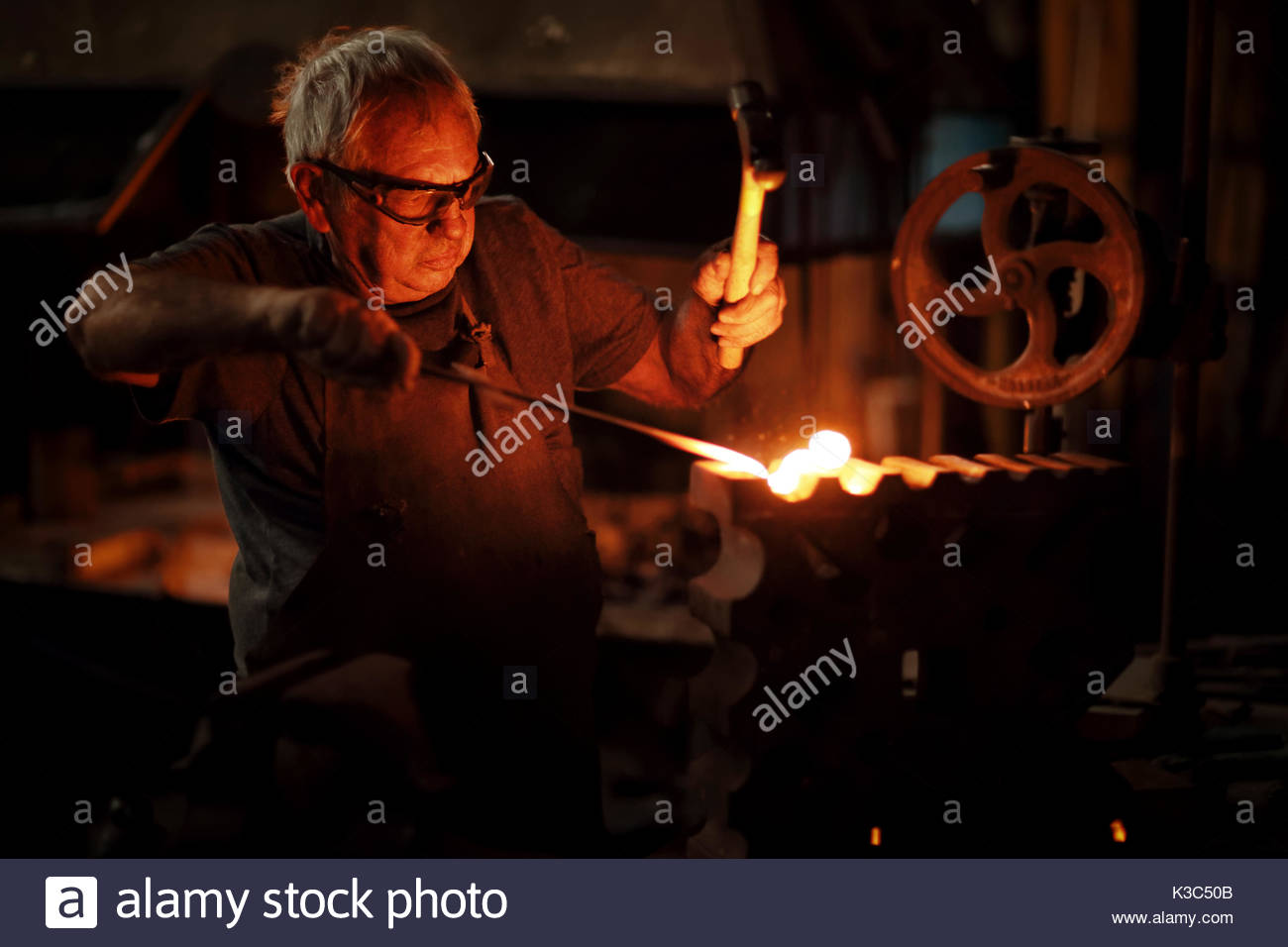 Authentic Old-Fashioned Blacksmith forging red hot molten iron with hammer in his old workshop - Stock Image