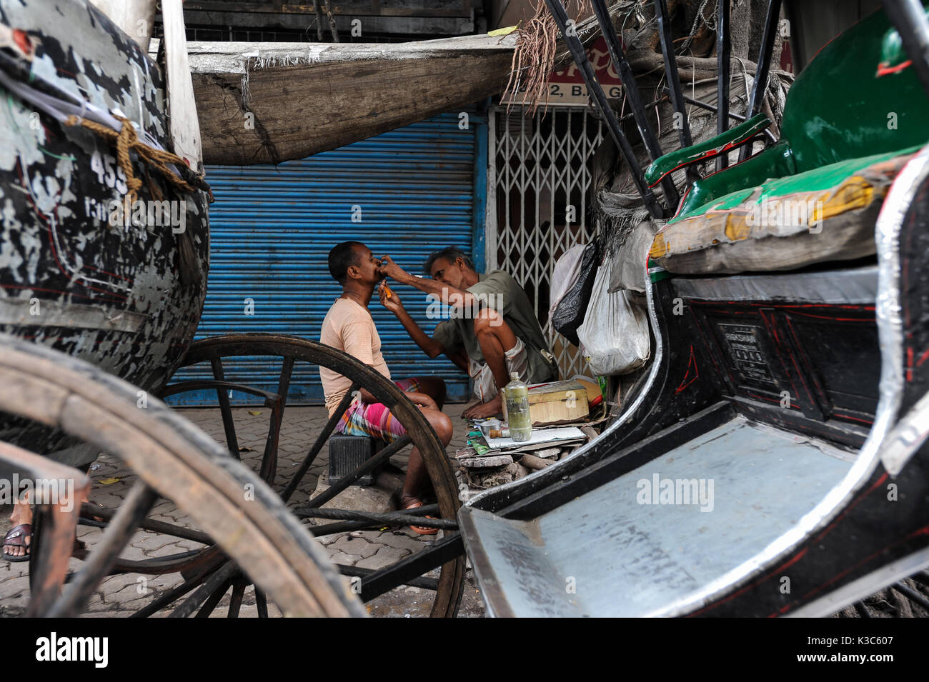 20.02.2011, Kolkata, West Bengal, India, Asia - A man gets shaved between rickshaws at a roadside in Kolkata. - Stock Image