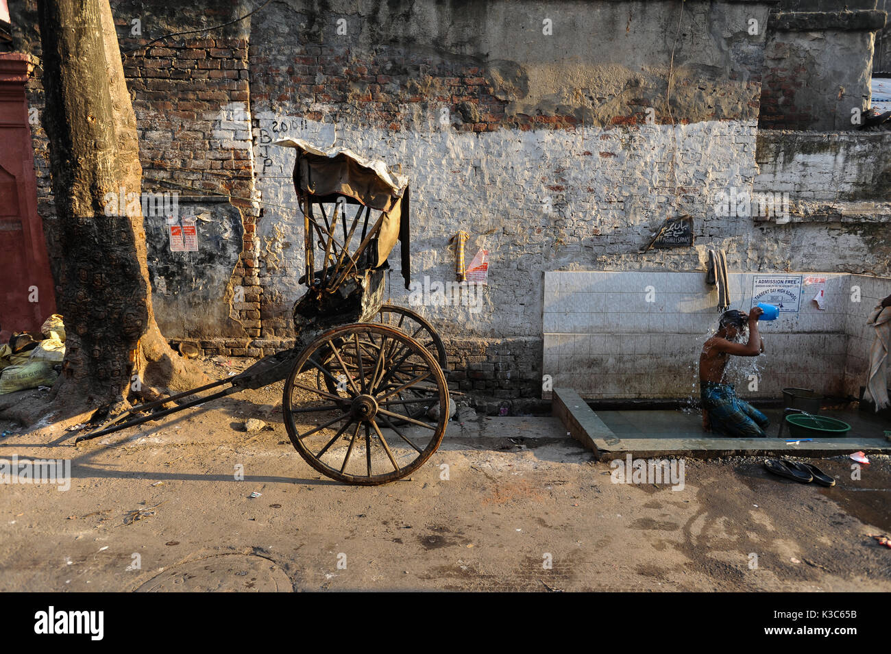 24.02.2011, Kolkata, West Bengal, India, Asia - A rickshaw puller showers next to his wooden rickshaw at a roadside - Stock Image