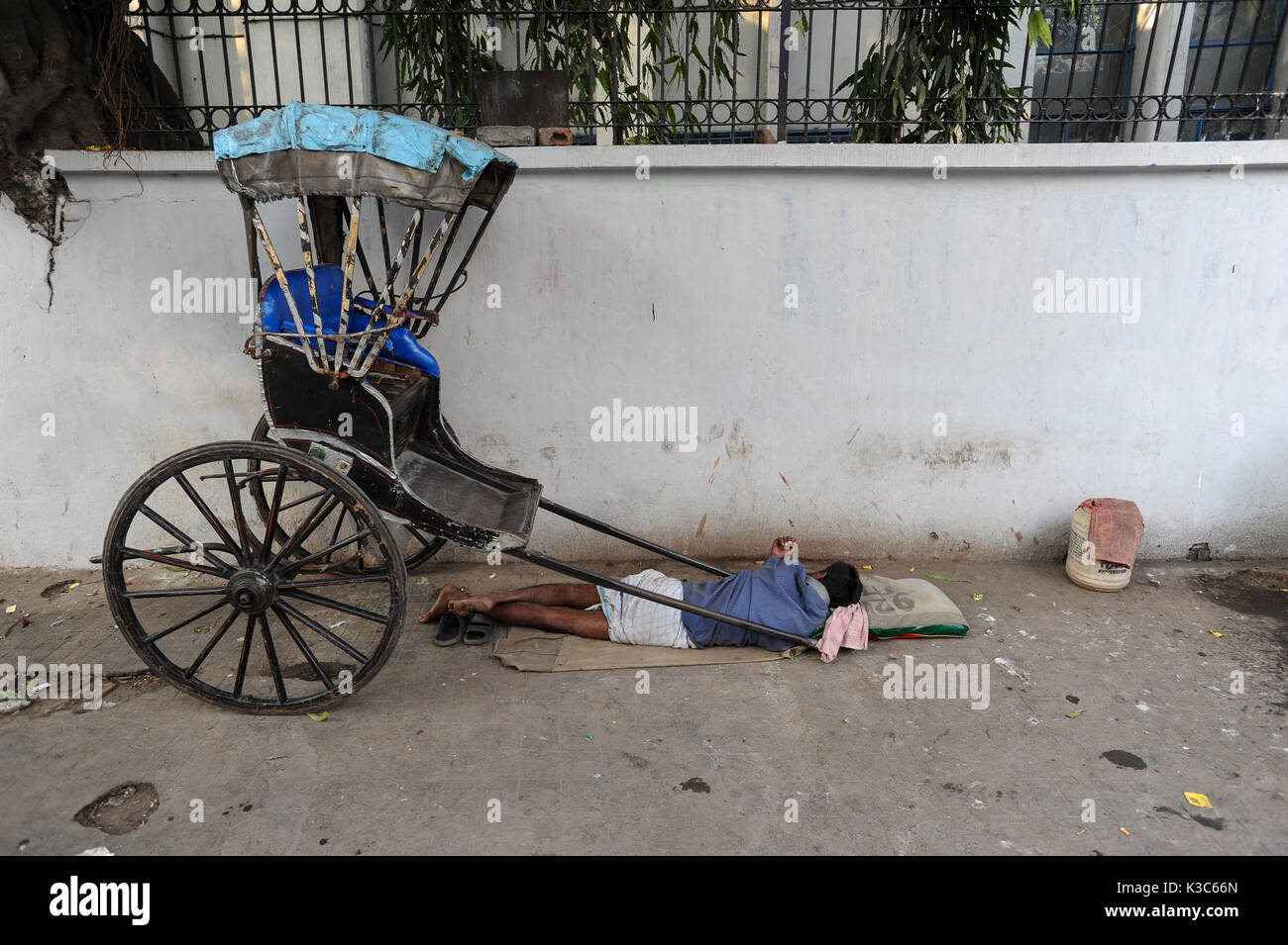 25.02.2011, Kolkata, West Bengal, India, Asia - A rickshaw puller sleeps next to his wooden rickshaw at a roadside - Stock Image
