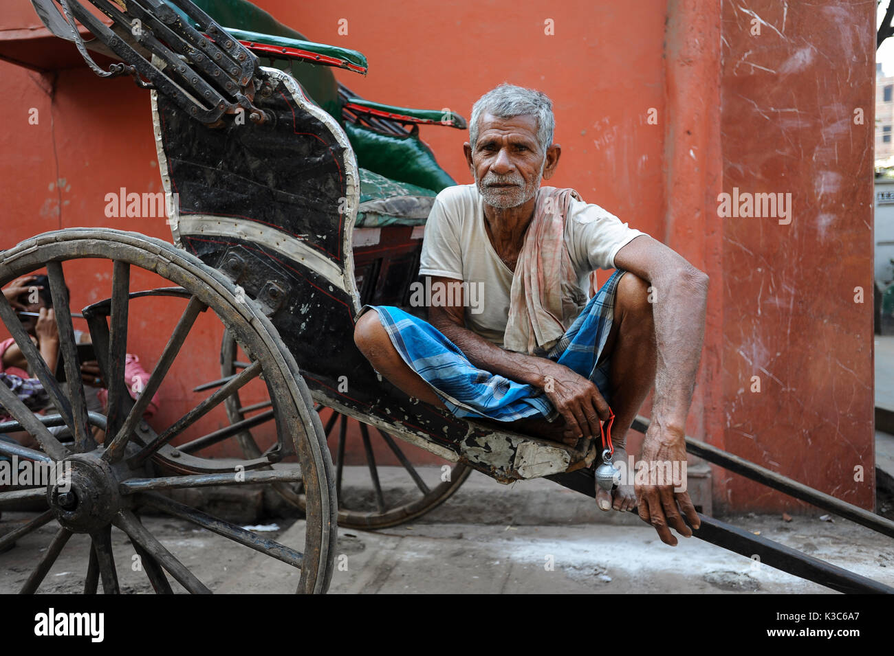 26.02.2011, Kolkata, West Bengal, India, Asia - A rickshaw puller waits for passengers at a roadside in Kolkata. - Stock Image
