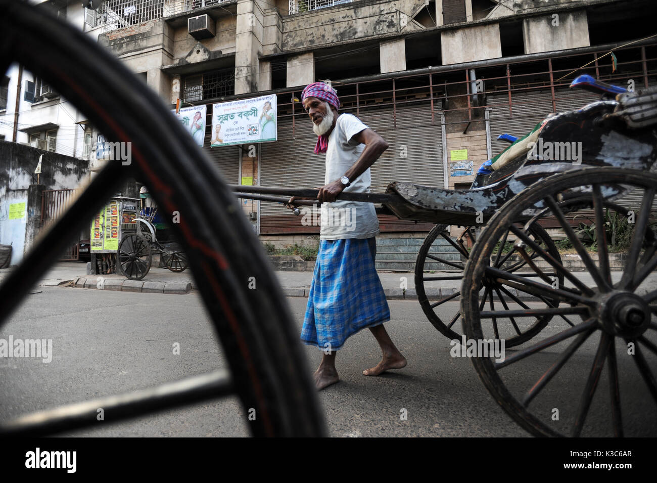 03.12.2011, Kolkata, West Bengal, India, Asia - Rickshaw puller Mohamed pulls his wooden rickshaw through the streets - Stock Image