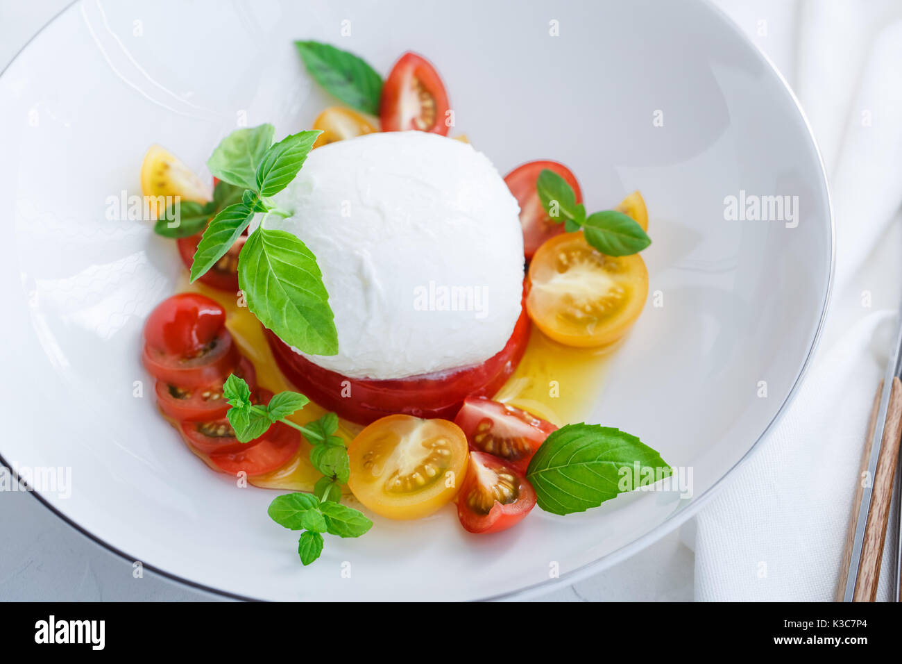 Caprese salad with red and yellow tomatoes, mozarella, basil and olive oil. Close view. White background. - Stock Image