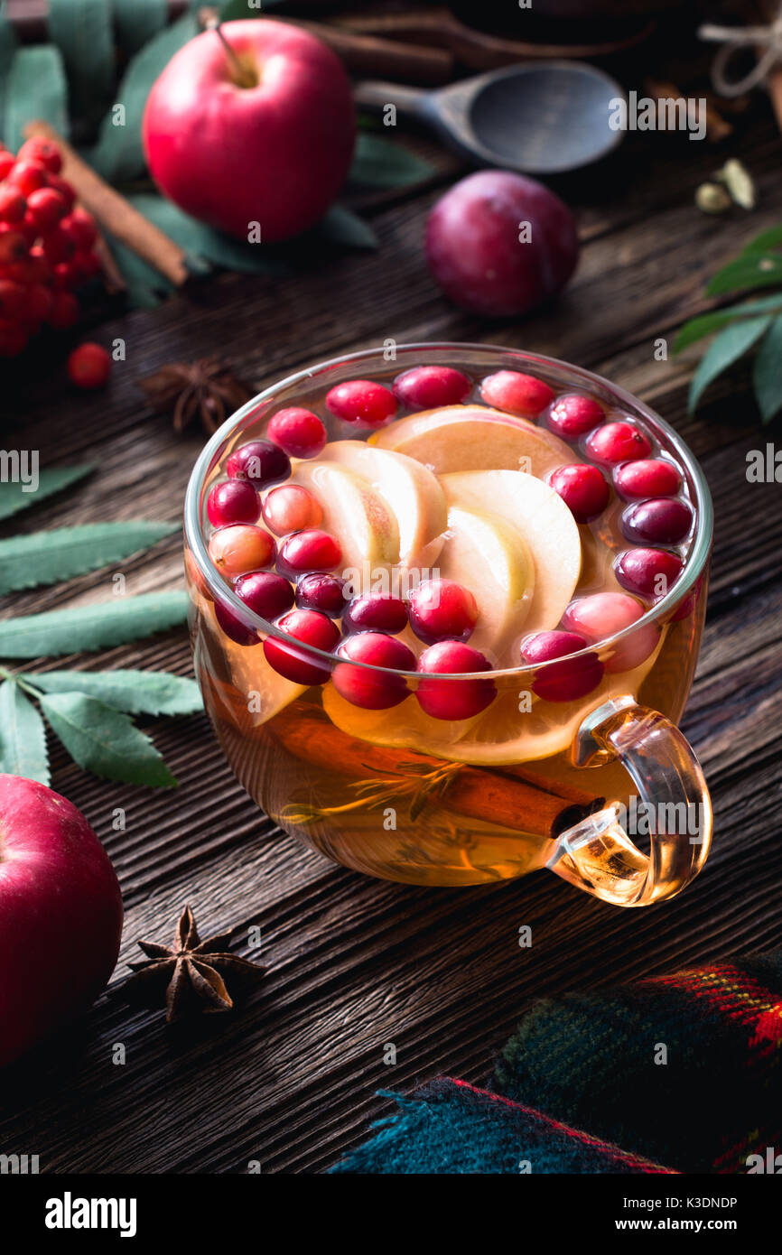 Warming winter berry tea with cranberries, apple, cinnamon, lemon, honey and thyme in a glass cup on wooden table. - Stock Image