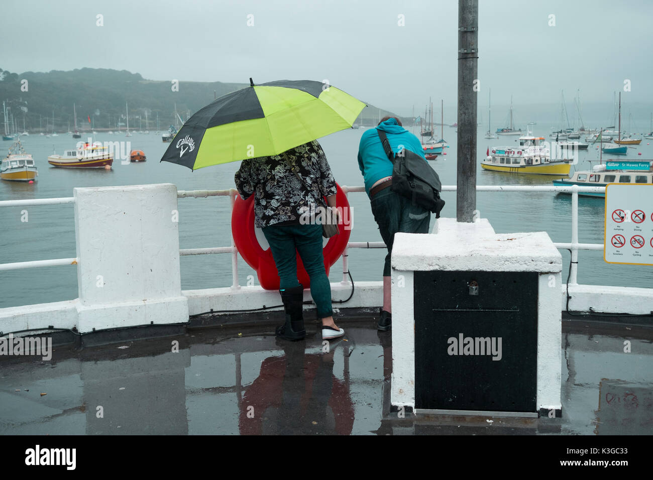 Falmouth, UK. 03rd Sep, 2017. A couple enjoy a wet walk along the Prince of Wales Pier, Falmouth Cornwall under Stock Photo