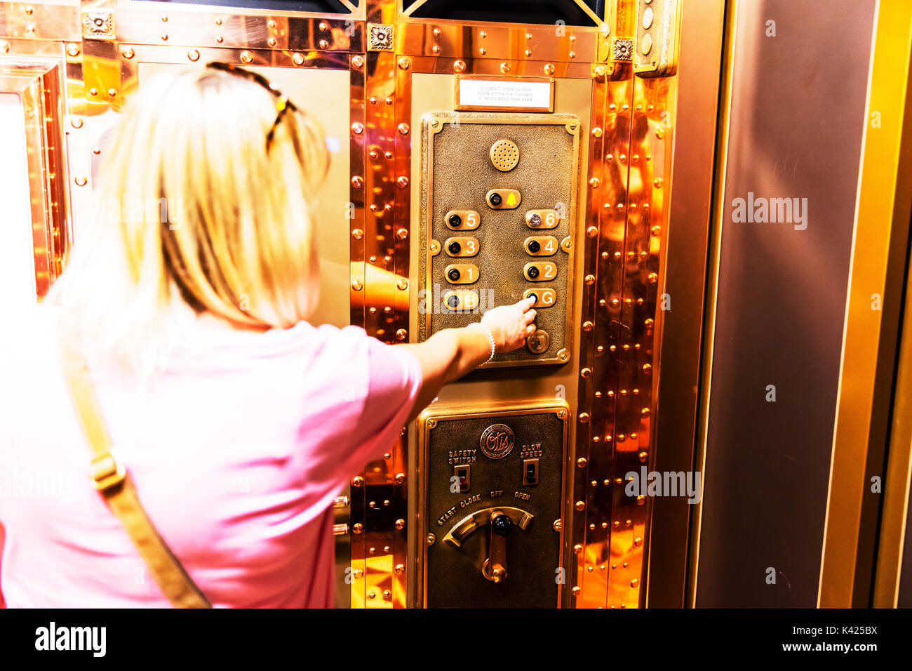 Pressing button in elevator, using elevator, selecting floor number in elevator, using lift, pressing button in - Stock Image