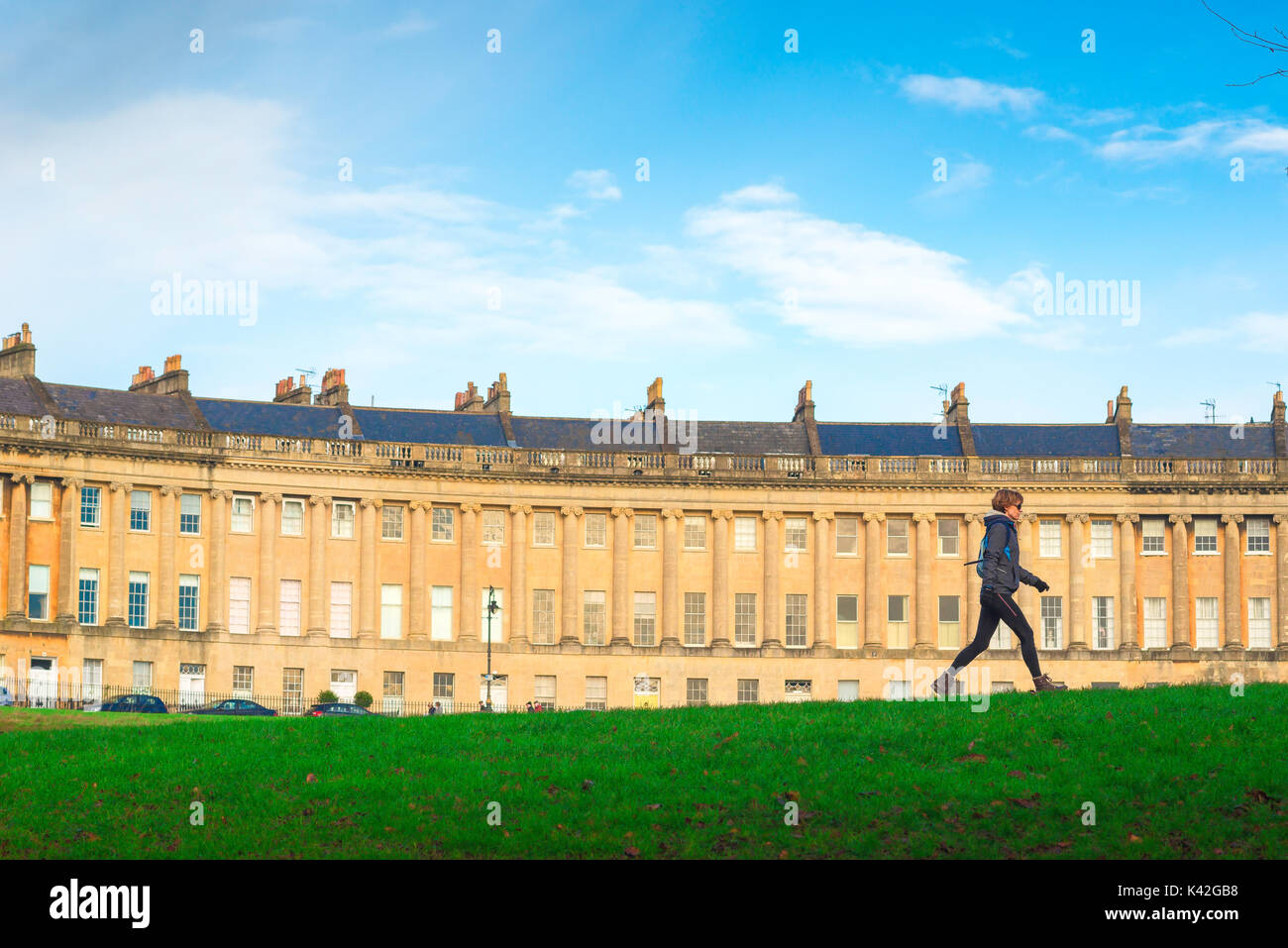 Bath city Georgian architecture, against the backdrop of the Royal Crescent, a woman walks briskly through Victoria Stock Photo