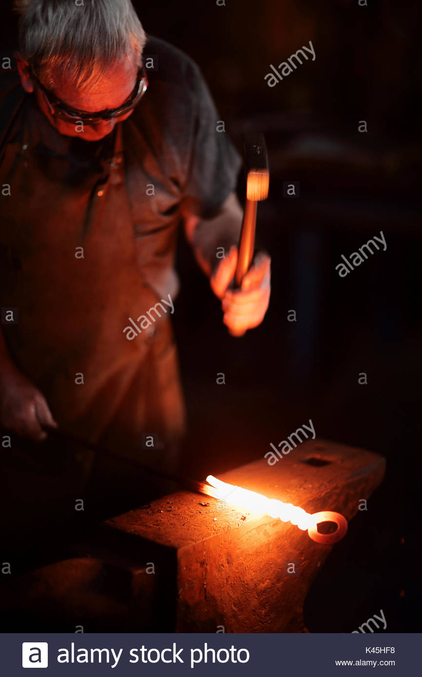 Close-up of  Blacksmith's hammer and hand forging red hot molten iron on the anvil - Stock Image