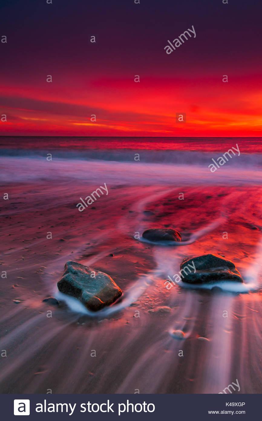 Storm sunrise on the sandy beach. Crimea - Stock Image