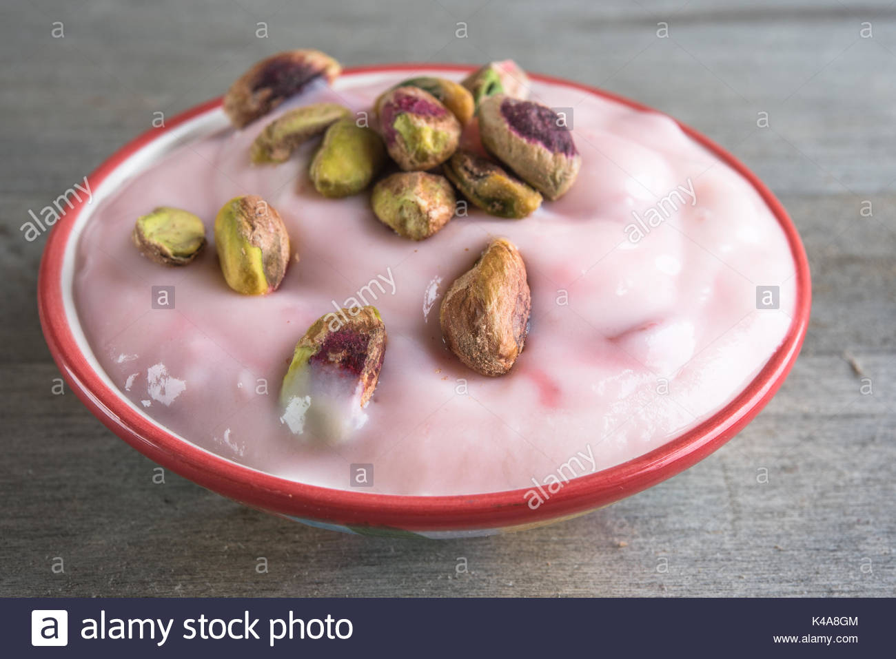 Healthy eating: strawberry yogurt with pistachio nuts. - Stock Image
