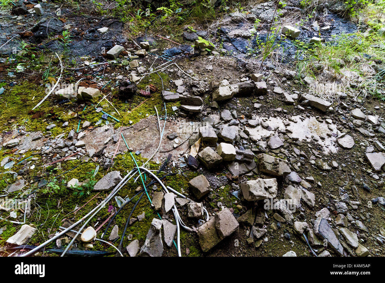 Rubble on the ground with broken bricks and stones and wires - Stock Image