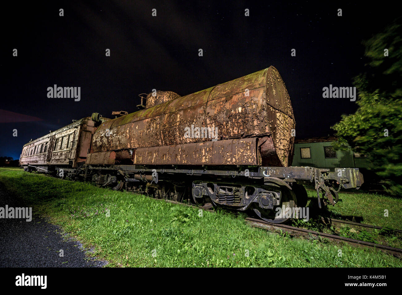 Decayed locomotive car at night - Stock Image