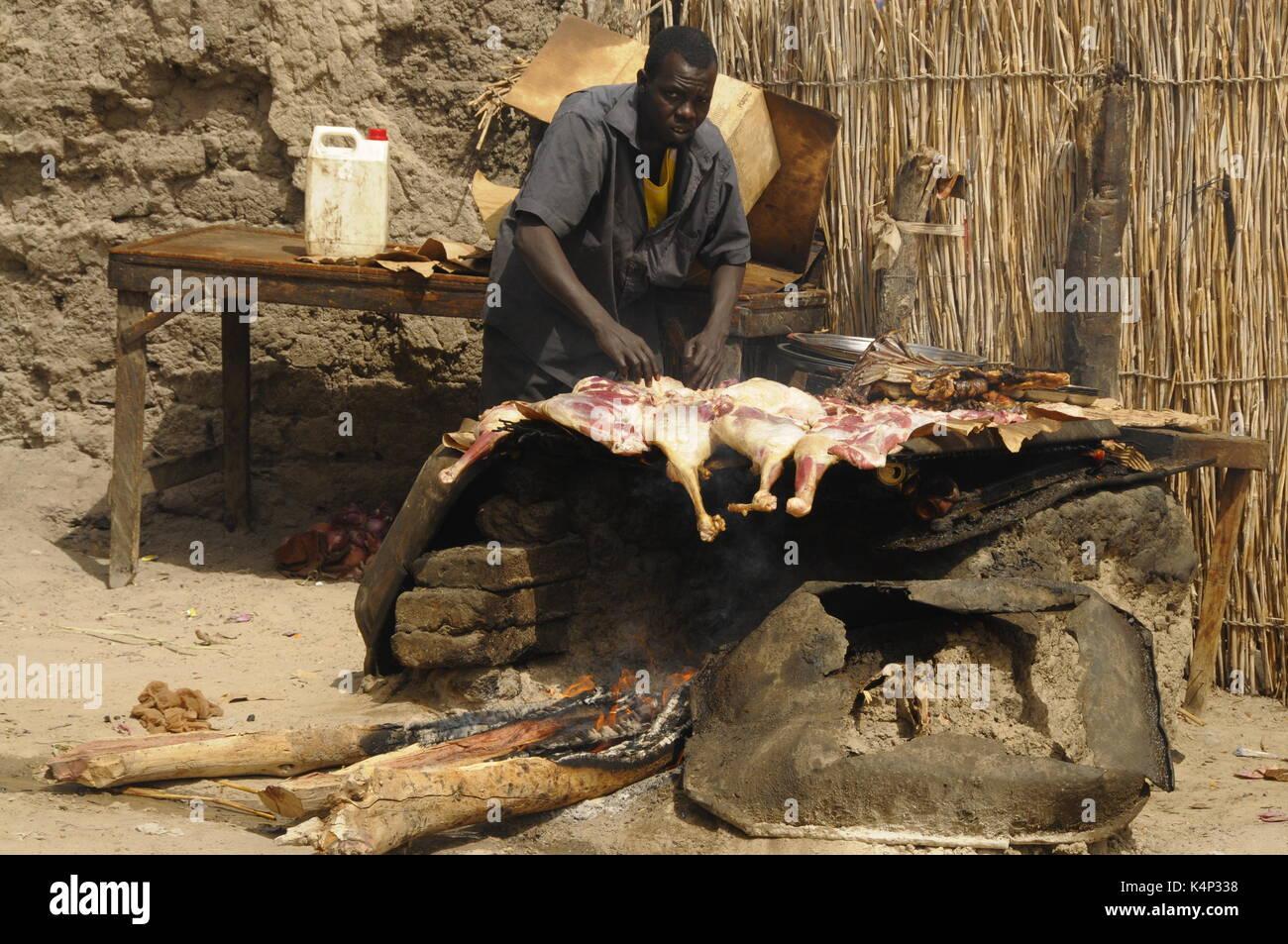 man frying lamb on a street of faya chad africa stock photo