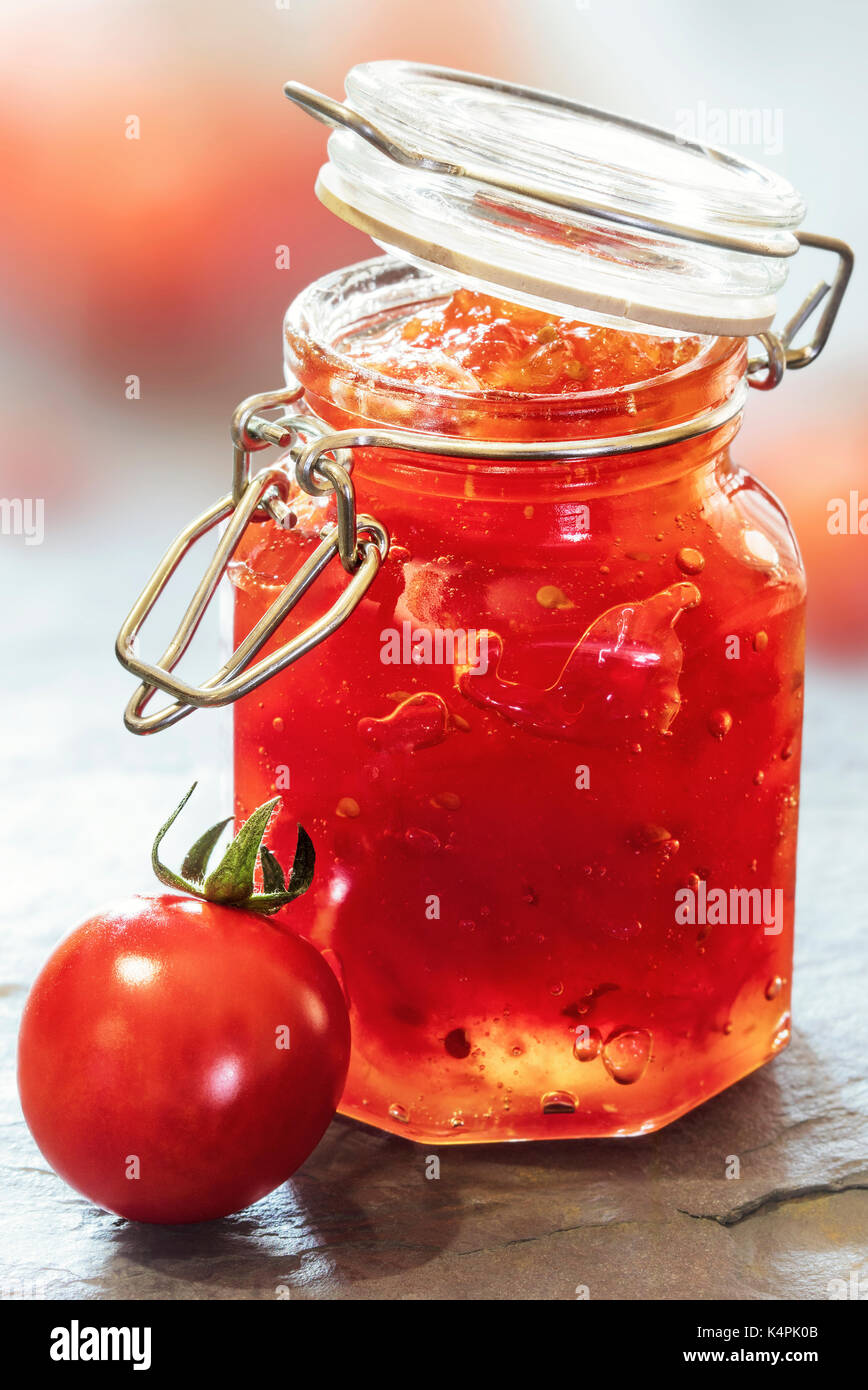 Tomato Jam in a glass jar on a slate table top - Stock Image