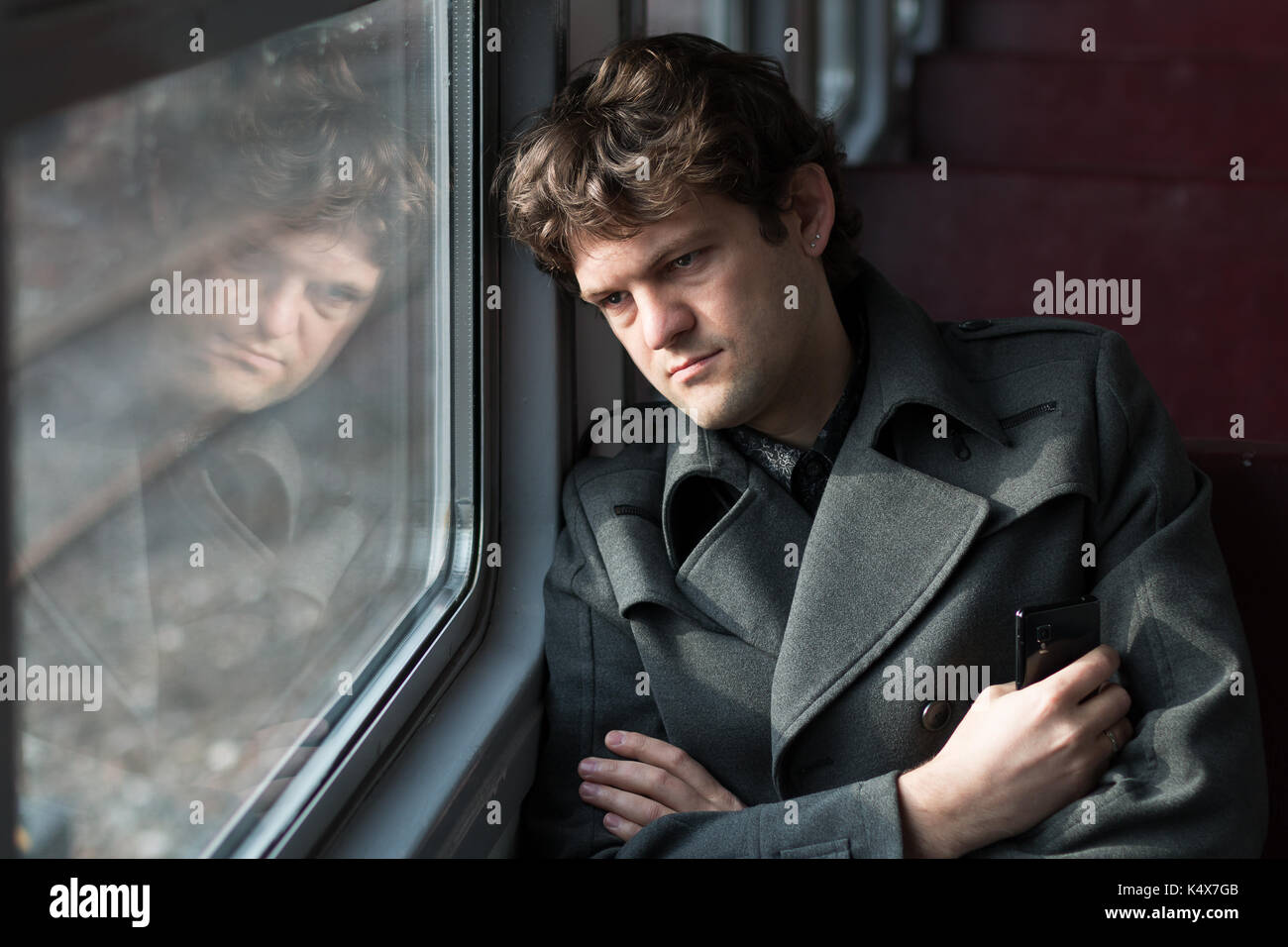 Traveling by train. Sad man traveling by train, looking through the window and thinking about unrequited love squeezing - Stock Image