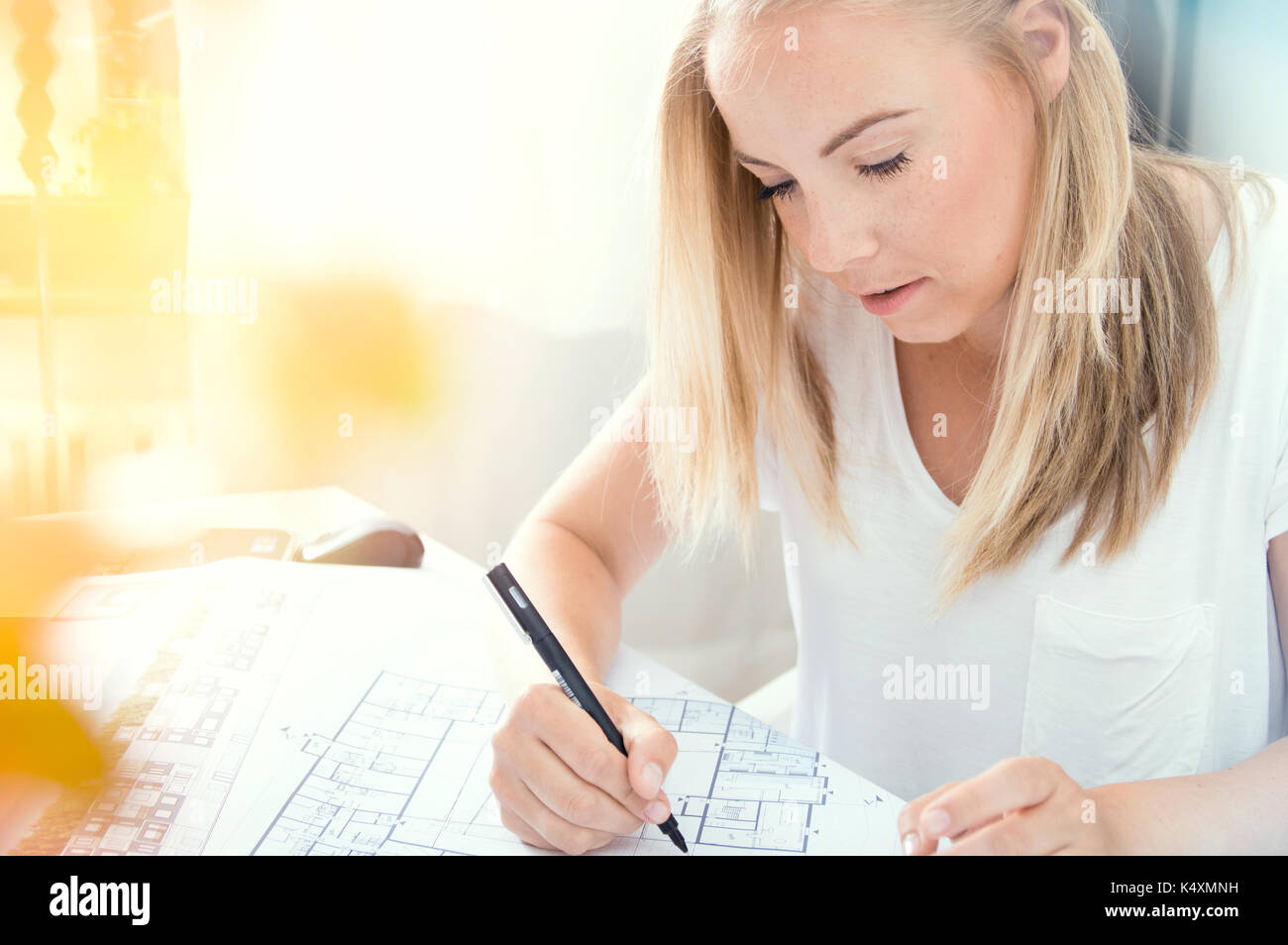 Young blonde architect is making professional architectural plan - Stock Image