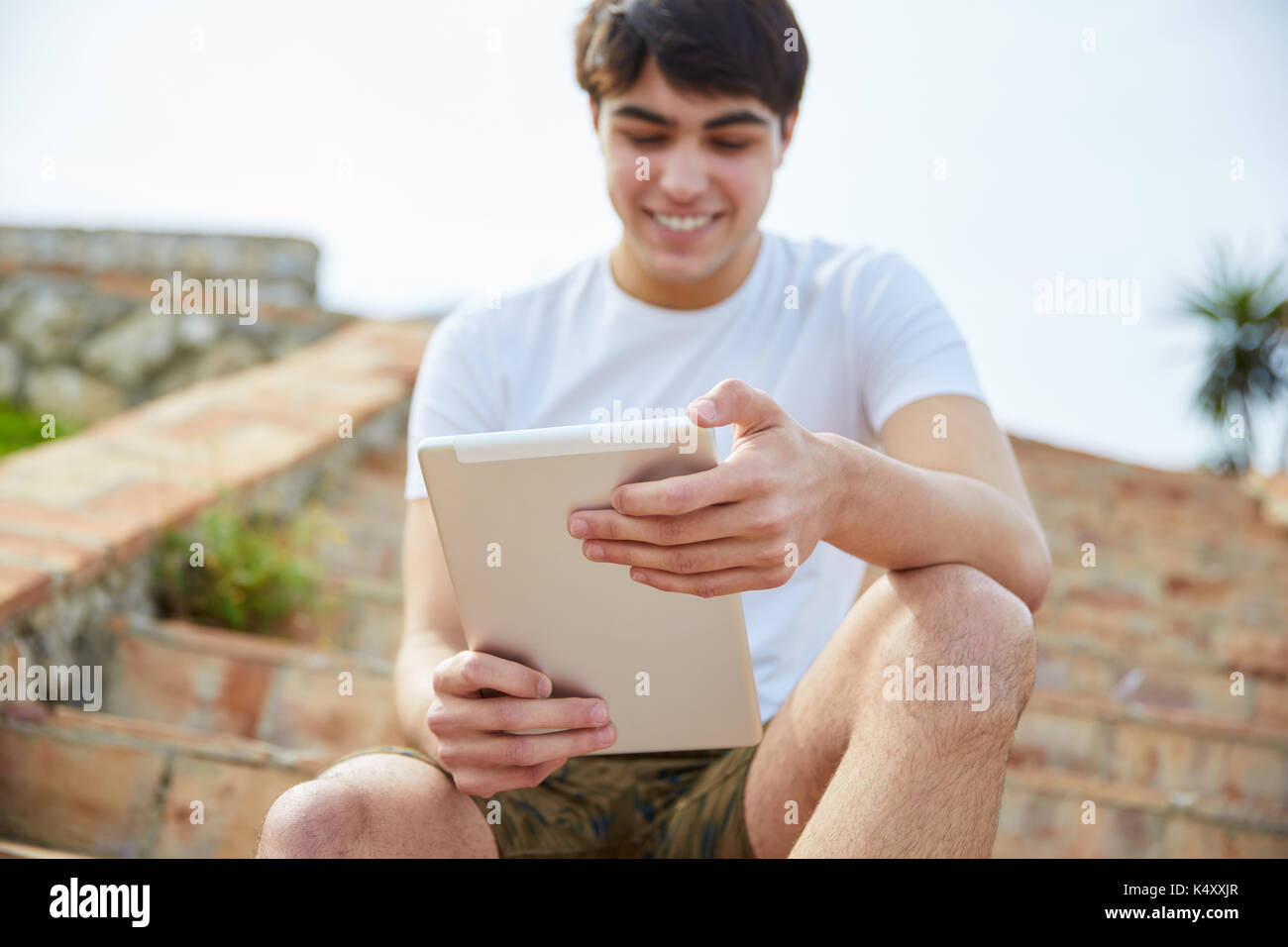 Portrait of young happy man sitting on stairs outside using tablet - Stock Image