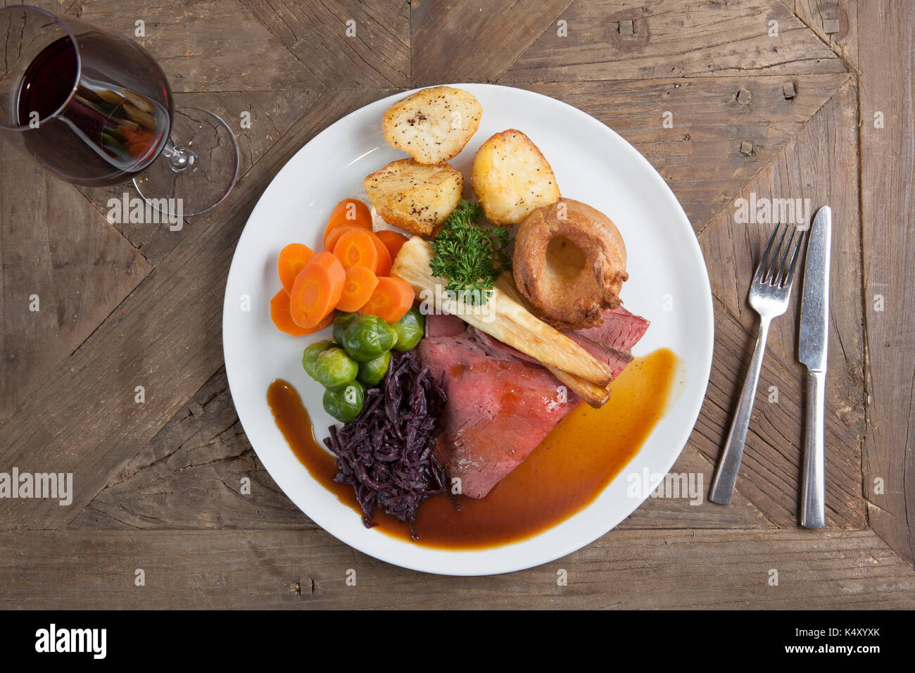 Roast beef dinner with gravy on a plate on a wooden table & Roast beef dinner with gravy on a plate on a wooden table Stock ...