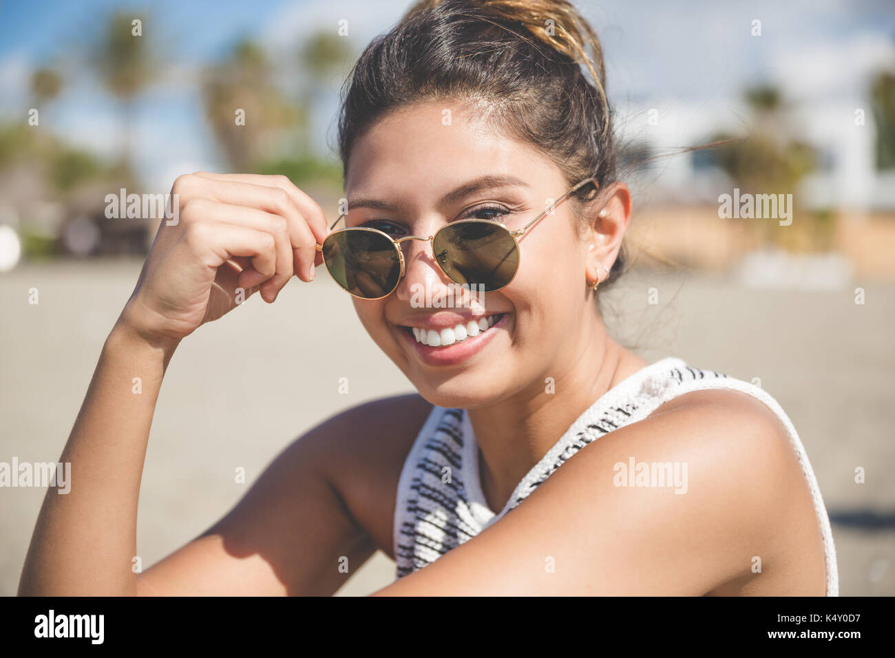 Close up portrait of young pretty woman holding sunglasses smiling - Stock Image