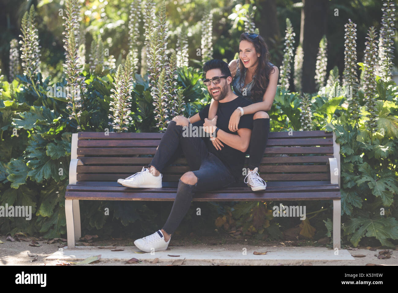 Portrait of laughing couple sitting together on bench - Stock Image