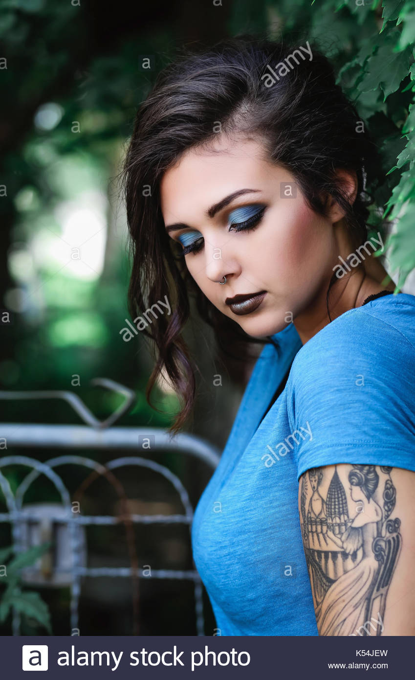 Young woman in blue looking down - Stock Image