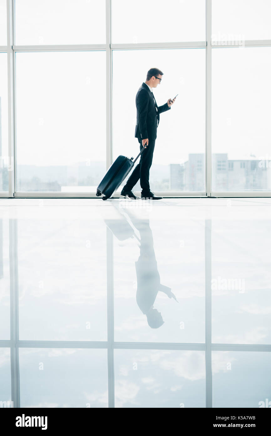 Businessman at international airport moving to terminal gate for airplane travel trip with phone in hand - Stock Image