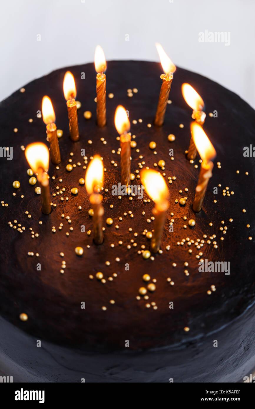 Black round birthday cake with burning golden candles on white background - Stock Image