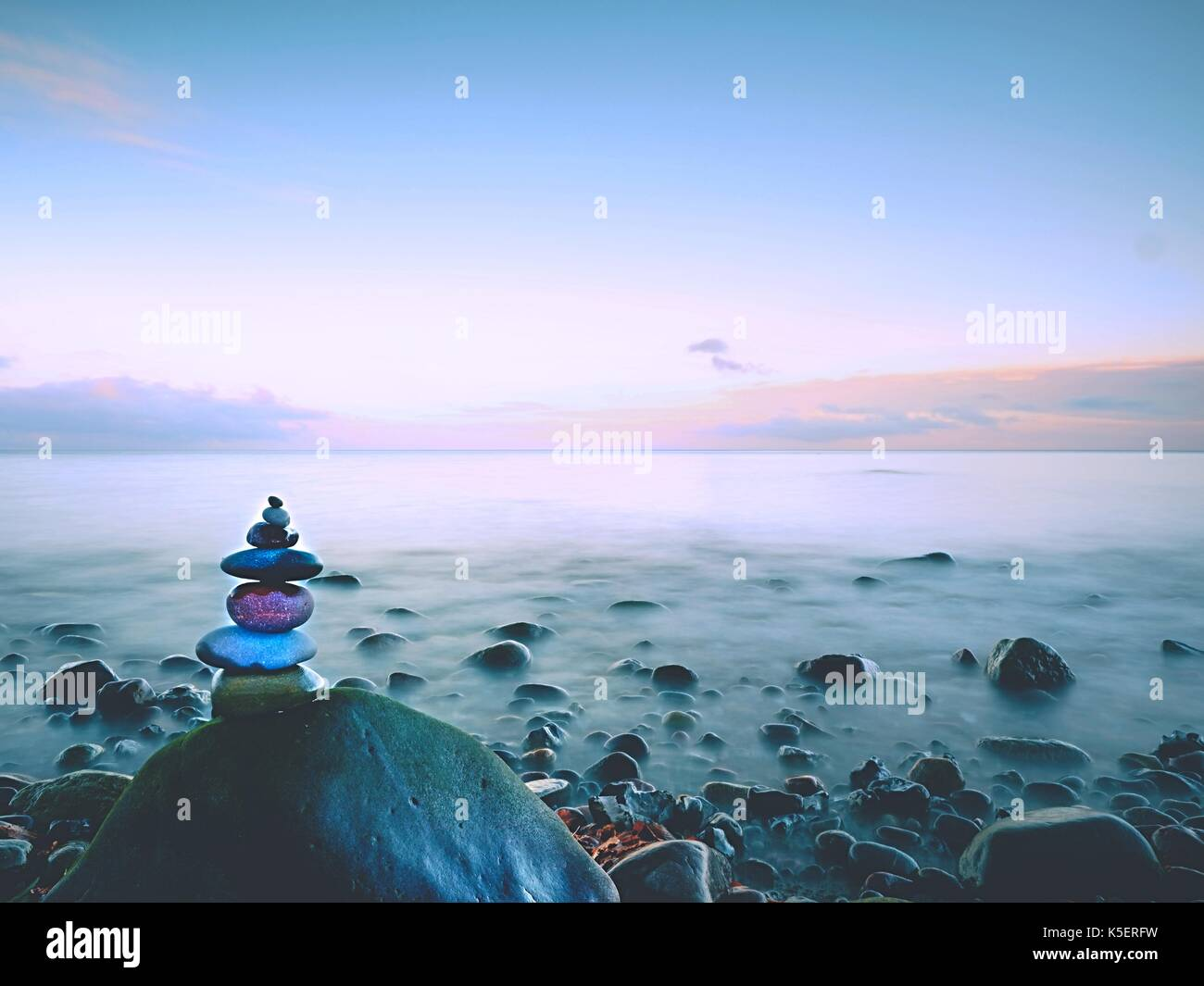 Rounded colorful stones stand in the form of pyramid big rounded stone at sea water - Stock Image