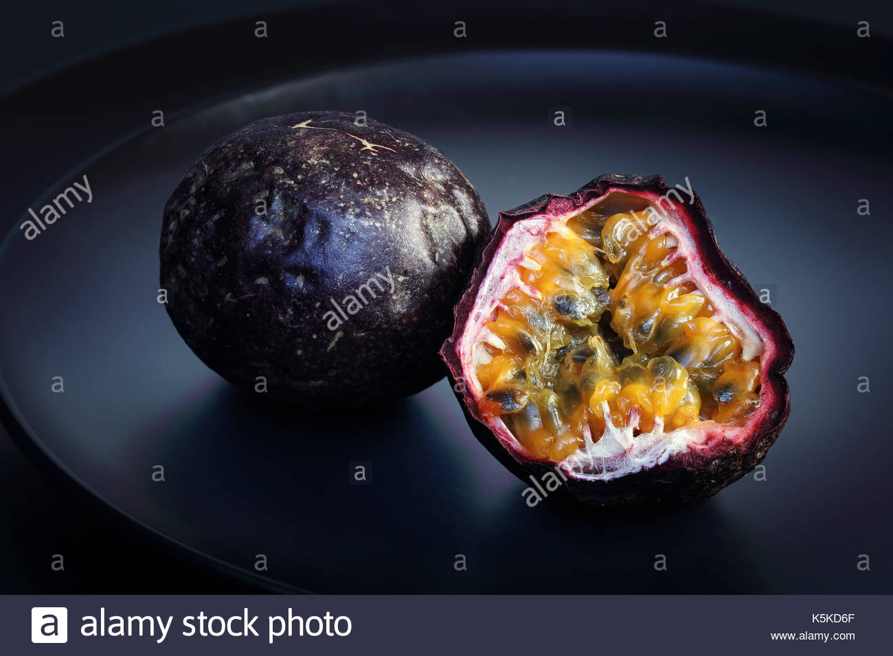 Purple Passion Fruit Halved and whole on a clean black plate - Stock Image