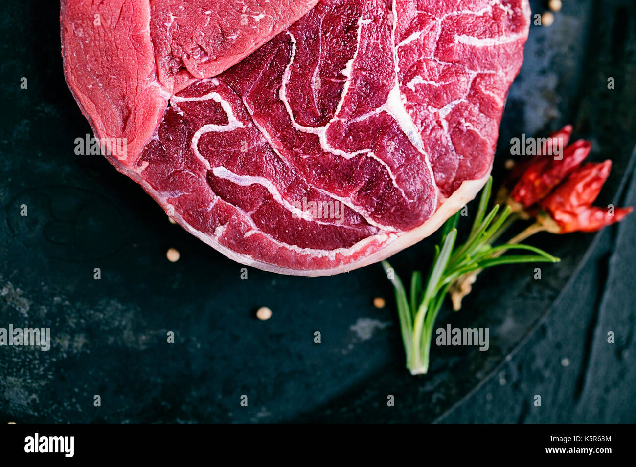 Meat. Raw meat. Beef steak on  black with herbs - Stock Image