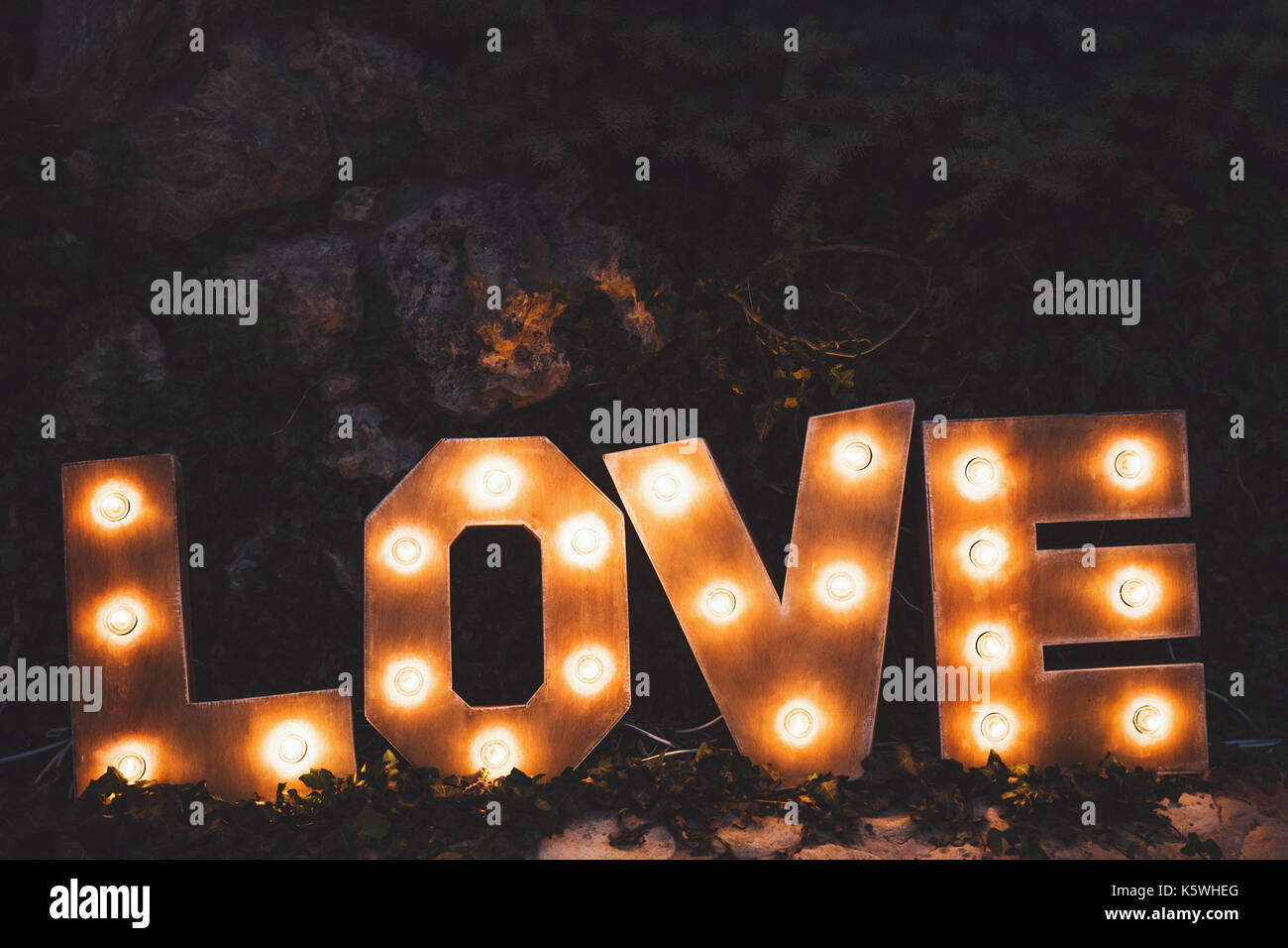 Word love consisting of the letters highlighted with bulbs standing on lawn at night - Stock Image