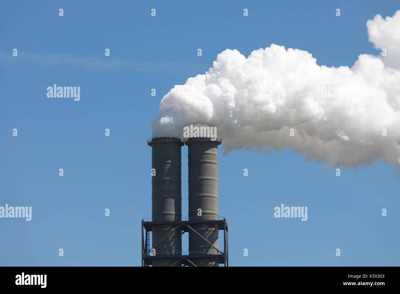 White Smoking industrial Chimney in front of a blue sky - Stock Image