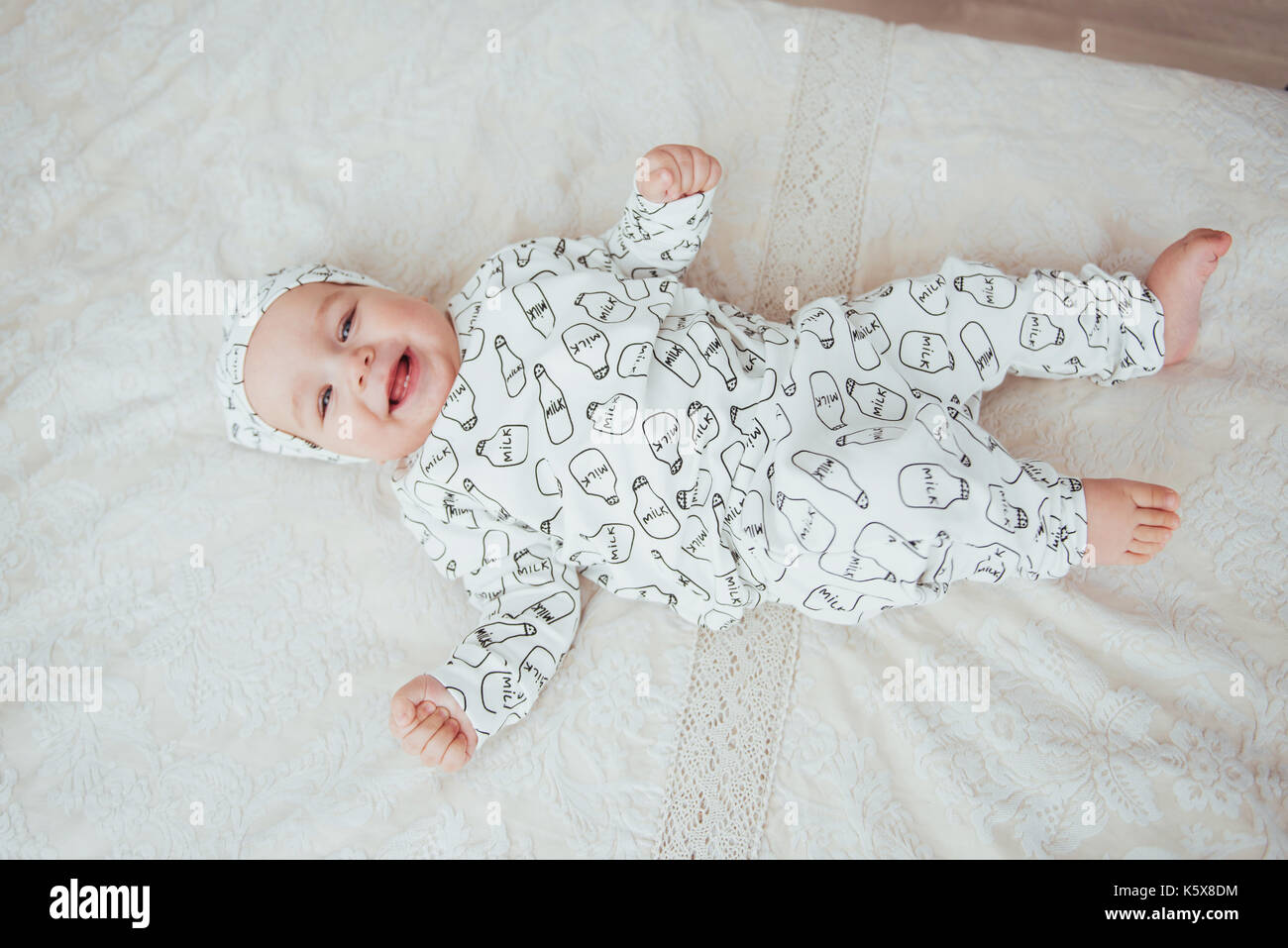 Newborn baby dressed in a suit on a soft bed in the studio. - Stock Image