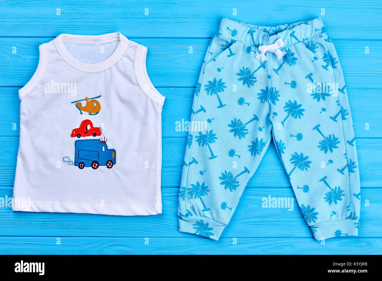 21b0dc9a7c25 Unisex baby summer outfit. New childs apparel on sale. Children cute summer  garment on blue wooden background.