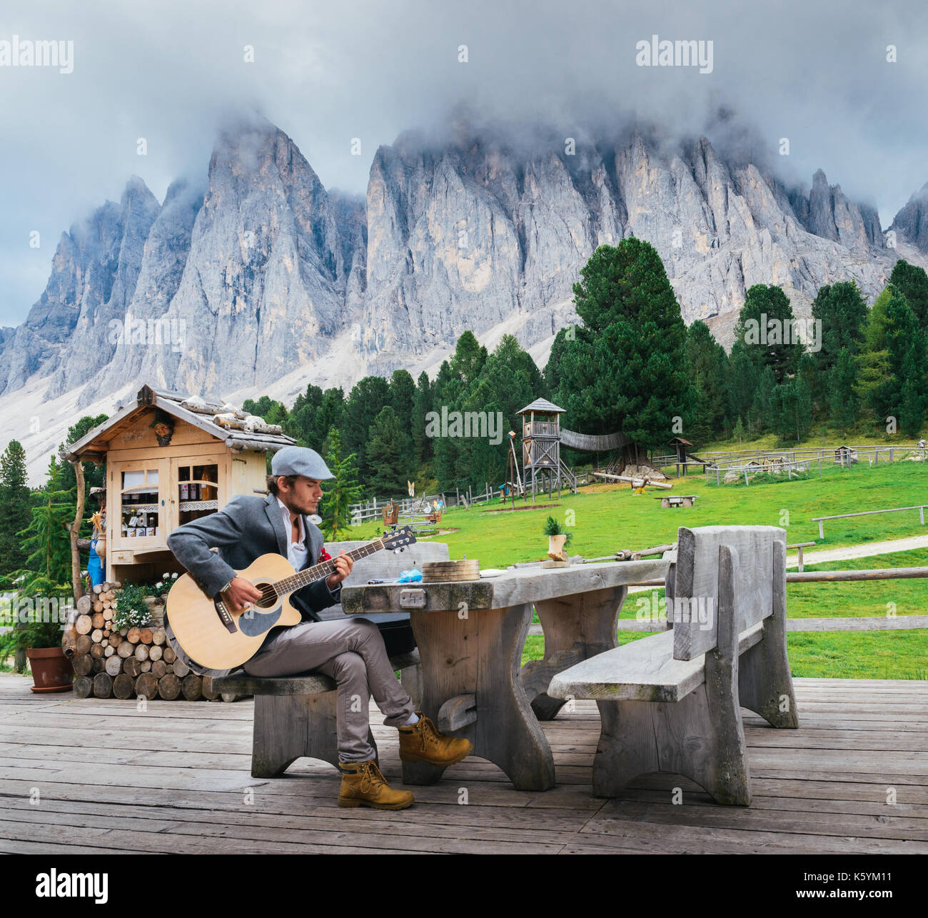 young-well-dressed-man-30-35-playing-a-guitar-with-italian-dolomites-K5YM11.jpg