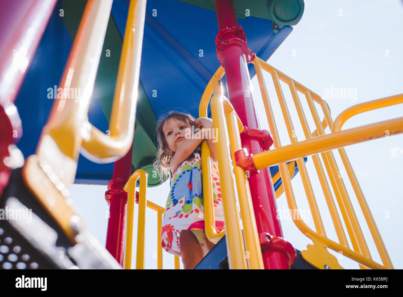 A toddler girl plays on playground equipment on a sunny day. - Stock Image