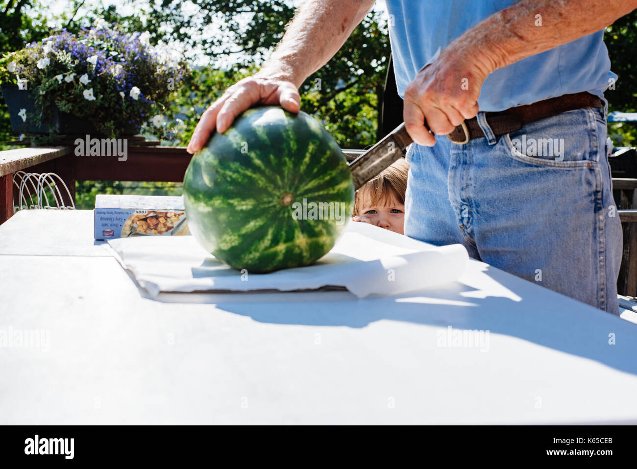 A man cuts a watermelon while a toddler watches. - Stock Image
