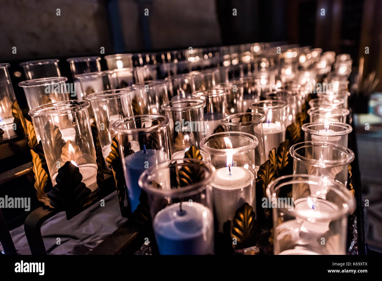Closeup side pattern of many white religious votive candles with yellow flame in church or cathedral - Stock Image