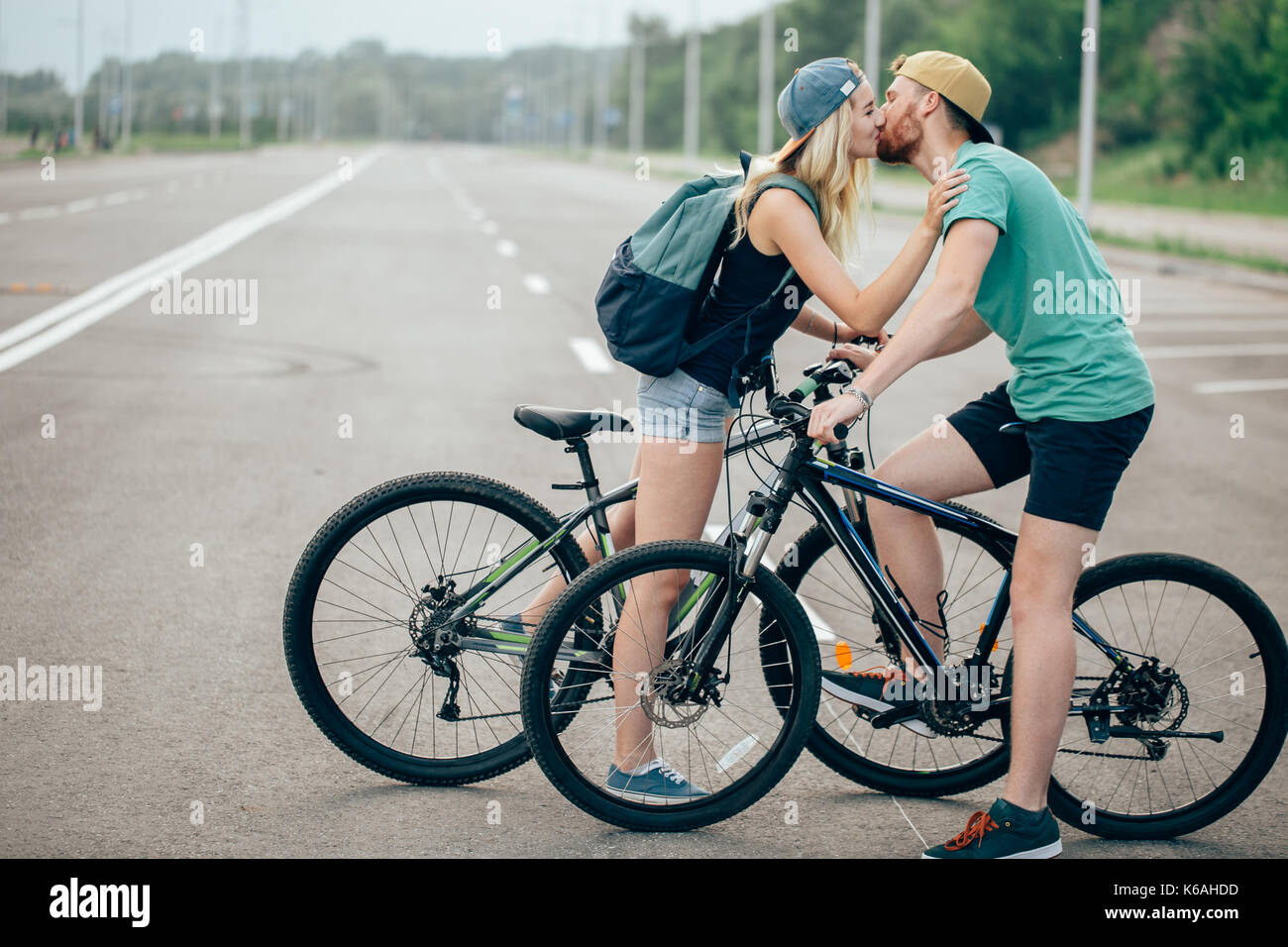 Beautiful young couple in love walking with bicycles, kissing and hugging. Stand near the bikes. The concept of - Stock Image