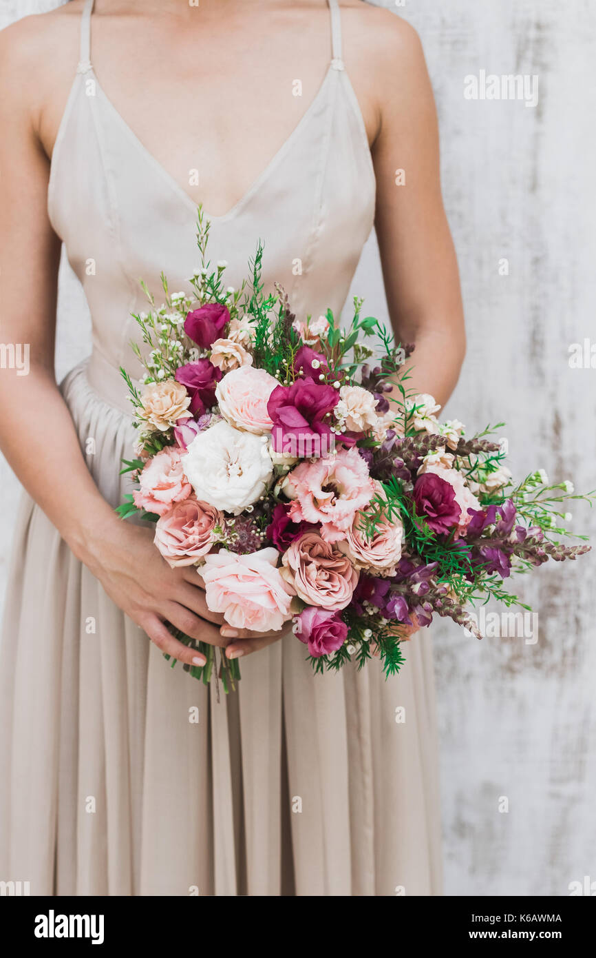 Сhic wedding bouquet of peonies and roses in hands of the bride - Stock Image