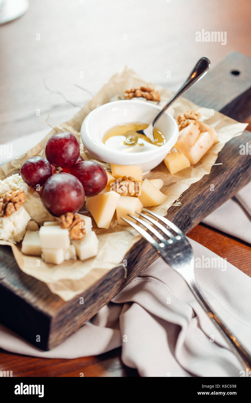 Appetizer bruschetta with pear, honey, hazelnuts and cottage cheese on old rustic wooden background, selective focus - Stock Image