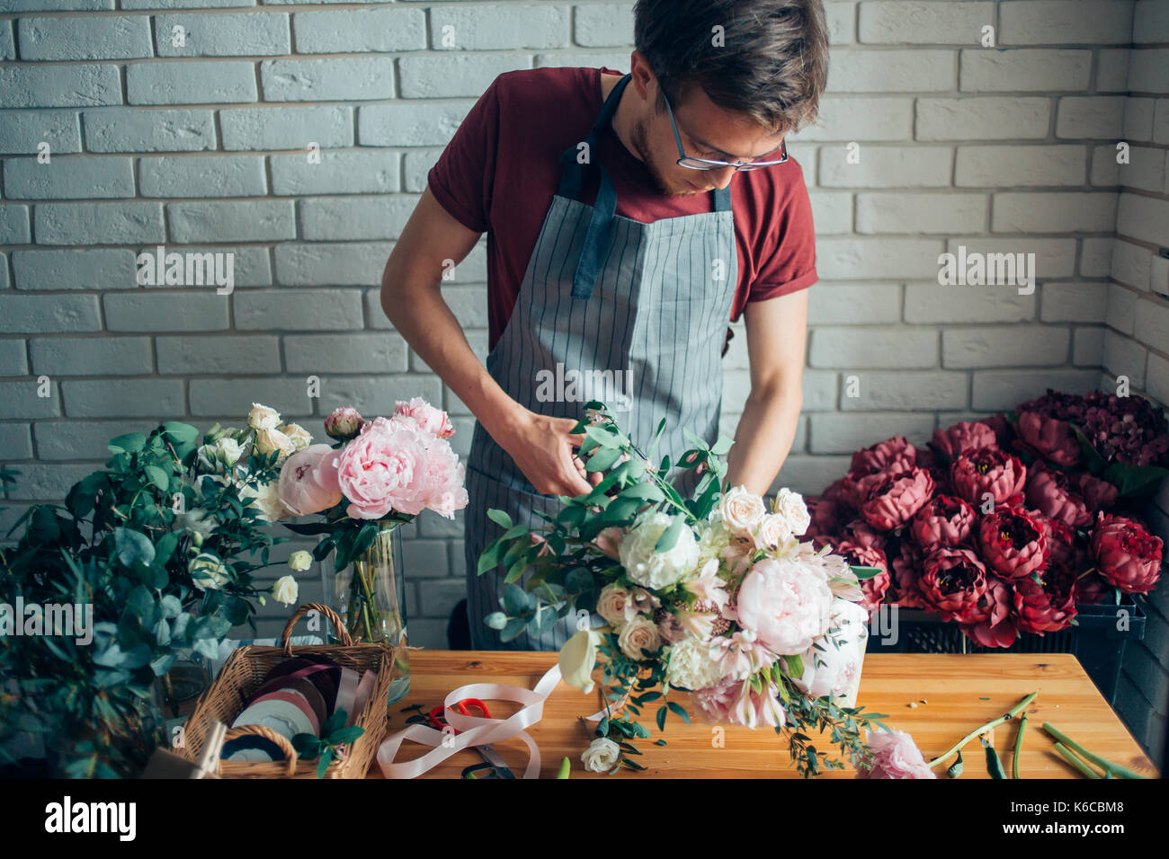 Young male florist working at counter in flower shop - Stock Image