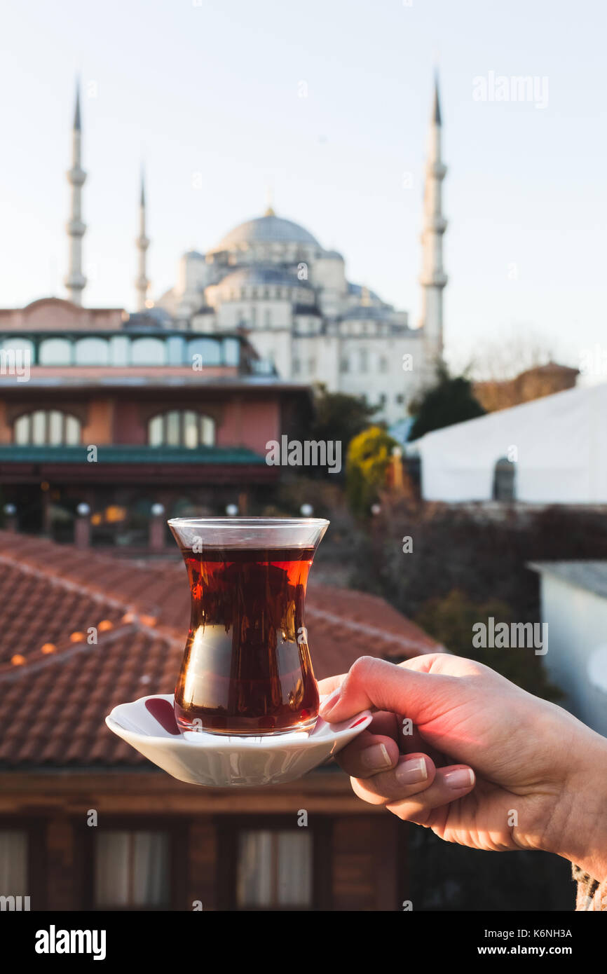 Woman holding cup of traditional Turkish tea on terrace with view of the Blue Mosque. Beautiful morning sunlight - Stock Image